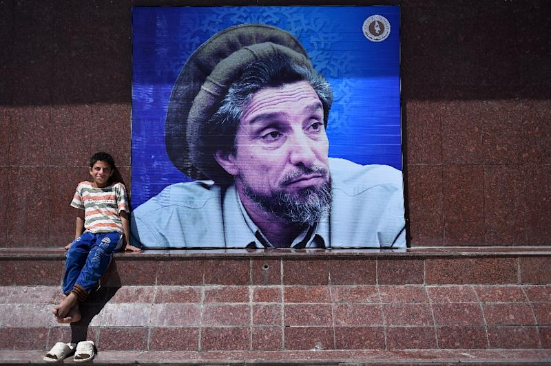 "An Afghan boy sits next to a poster in Kabul bearing the image of the late resistance leader Ahmad Shah Massoud, the ""Lion of Panjshir"" (AFP Photo/Wakil Kohsar)"