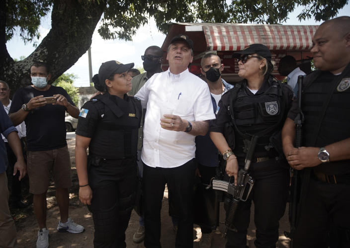 "Brazil's President Jair Bolsonaro, center, talks with police officers after voting during the run-off municipal elections in Rio de Janeiro, Brazil, Sunday, Nov. 29, 2020. Bolsonaro, who sometimes has embraced the label ""Trump of the Tropics,"" said Sunday he'll wait a little longer before recognizing the U.S. election victory of Joe Biden, while also echoing President Donald Trump's allegations of irregularities in the U.S. vote. (AP Photo/Silvia Izquierdo)"