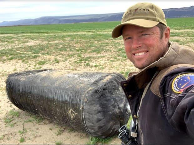 Robert Ward beside a pressure tank that was part of the Falcon 9 rocket that fell from the sky during re-entry and landed in eastern Washington state on March 25.  (Robert Ward - image credit)