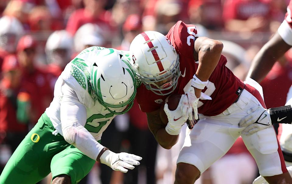 Austin Jones of the Stanford Cardinal is tackled by Oregon's Kayvon Thibodeaux at Stanford Stadium.