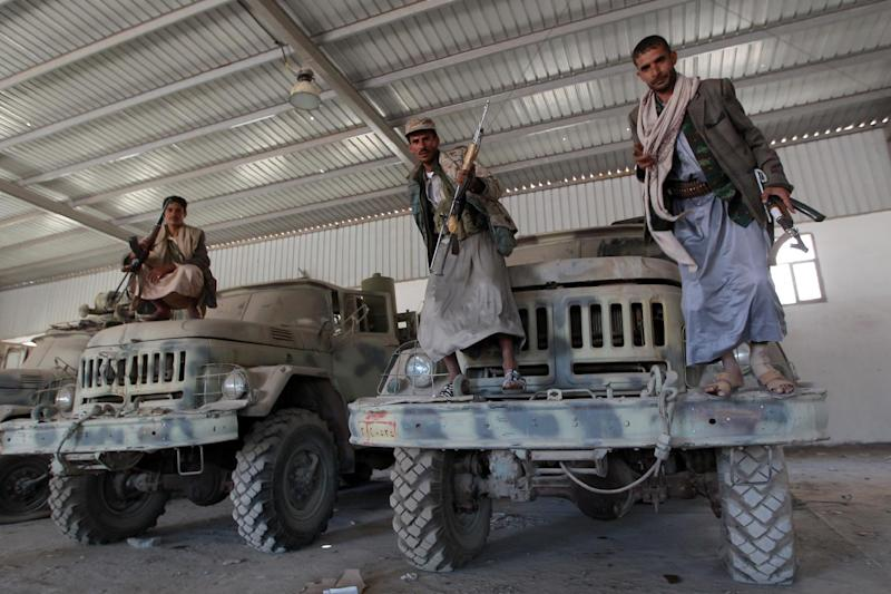 Yemeni Huthi rebels pose on military vehicles at an army base which they captured just hours before the signing a UN-brokered peace agreement on September 22, 2014 in Sanaa (AFP Photo/Mohammed Huwais)
