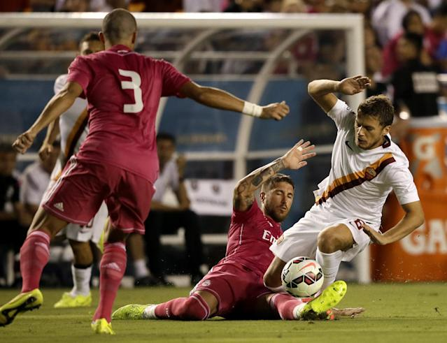 Real Madrid's Pepe (3) watches as Sergio Ramos, bottom, stops Roma forward Aden Ljajic (8) from moving the ball up field in the first half of a Guinness International Champions Cup soccer tournament match, Tuesday, July 29, 2014, in Dallas. (AP Photo/Tony Gutierrez)