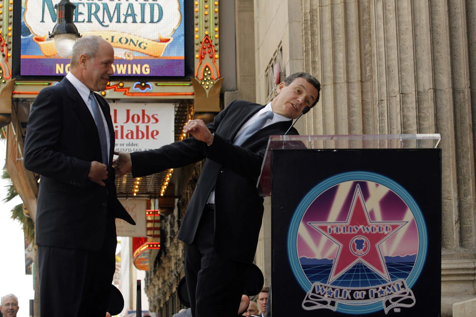 Bob Iger, President and CEO of The Walt Disney Co., right, jokes with Michael Eisner, former Disney CEO, about  wearing the same suit and tie, during a ceremony honoring Eisner with a star on the Hollywood Walk of Fame in Los Angeles, Friday, April 25, 2008. (AP Photo/Damian Dovarganes)