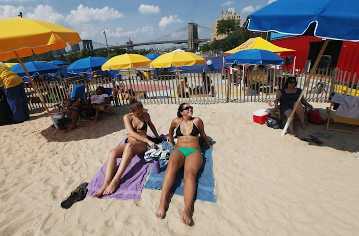 People relax in the sand at the Brooklyn Bridge Park pop-up pool on July 16, 2012 in the Brooklyn borough of New York City. A heat advisory was issued in the city again today as high temperatures were expected in the 90?s the next three days. (Photo by Mario Tama/Getty Images)