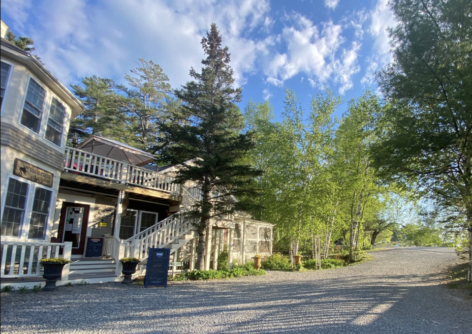 Pictured is the outside of Big Moose Inn, where the wedding took place, among several lush trees.