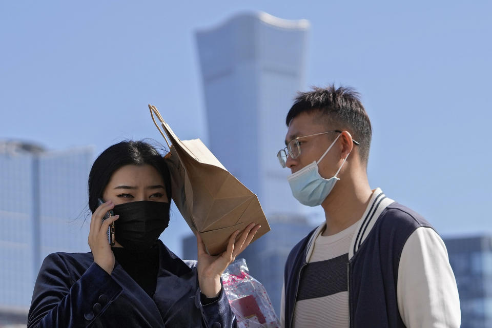 A man and a woman wearing face masks to help curb the spread of the coronavirus, walk across an intersection against the Central Business District in Beijing, Tuesday, Oct. 12, 2021. (AP Photo/Andy Wong)