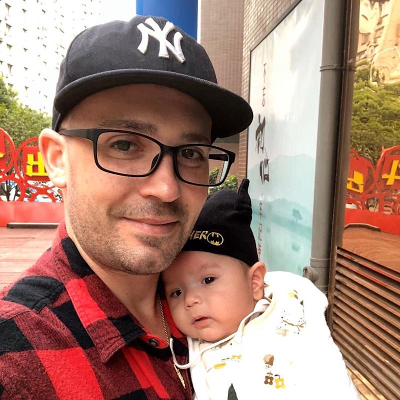 IMAGE: Christopher Suzanne holding his infant son in China.