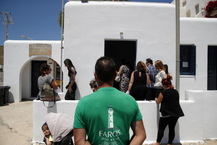 In this Monday, May 25, 2020 photo, local residents wait to be tested for coronavirus, on the Aegean Sea island of Folegandros, Greece. Using dinghies, a GPS, and a portable refrigerator, state doctors have launched a COVID-19 testing drive on islands in the Aegean Sea ahead of the holiday season. The first round of testing was completed after trips to the islands of Milos, Kimolos, Folegandros, and Sikinos. (AP Photo/Thanassis Stavrakis)