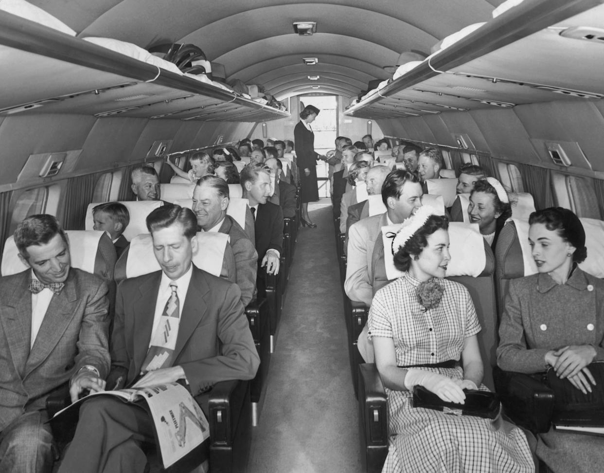 Passengers, seated two to a row, talk with their inflight neighbors aboard a Mainliner Convair aircraft as the flight attendant works at the back of the plane in the late 1940s.
