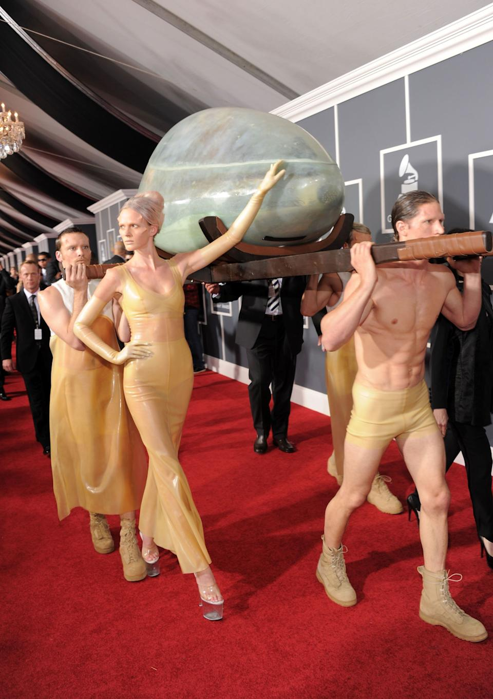 Lady Gaga arrives on the red carpet at the 2011 Grammy Awards in an egg carried by a group of latex-clad helpers.