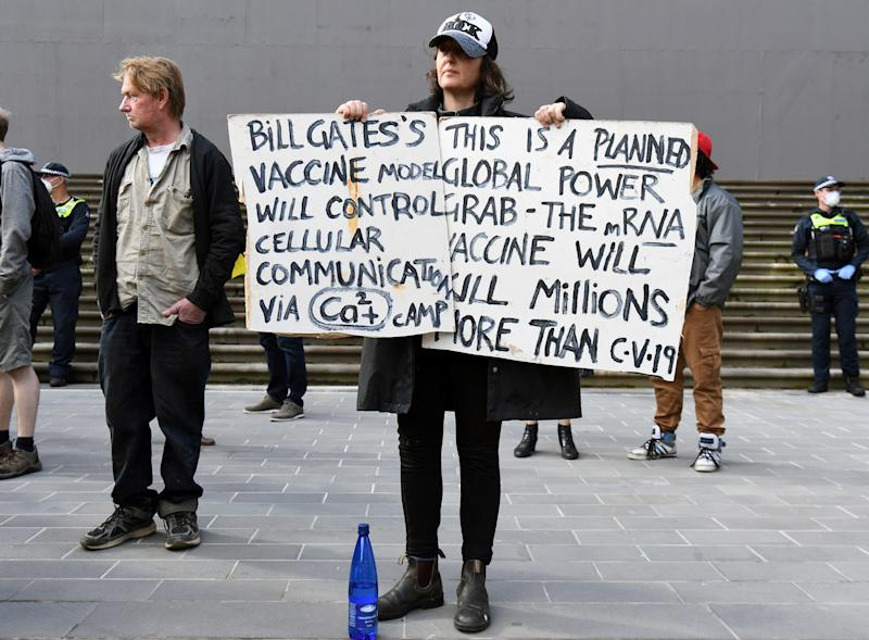 Anti-lockdown protesters hold placards on the steps of Victoria's state parliament in Melbourne on May 10, 2020 before police arrested 10 protesters - Hundreds of people gathered to protest the state's tough lockdown laws as well as 5G, vaccinations and coronavirus being a hoax. (Photo by William WEST / AFP) (Photo by WILLIAM WEST/AFP via Getty Images)