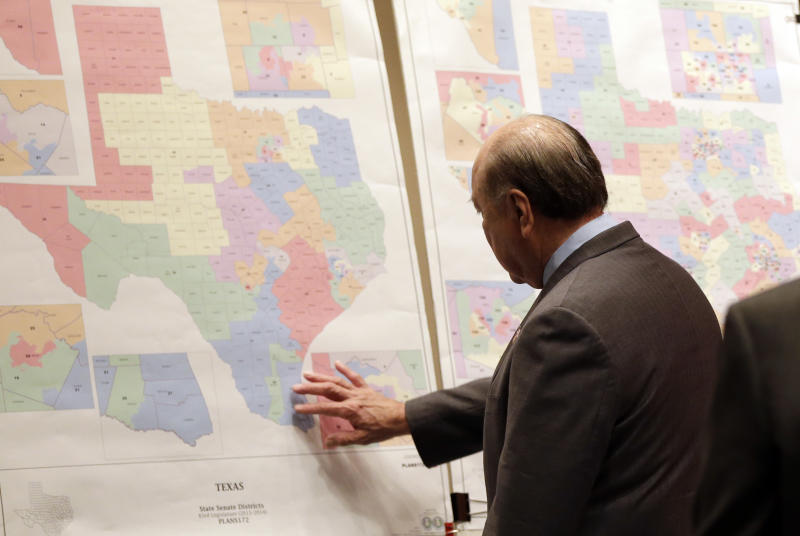 "File - In this May 30, 2013 file photo, Texas state Sen. Juan ""Chuy"" Hinojosa looks at maps on display prior to a Senate Redistricting committee hearing, in Austin, Texas. Attorney General Eric Holder says Texas is the first place that he will intervene to defend against what he calls attacks on the voting rights of minorities, but it is also the only state where the federal government has a clear opportunity to get involved, experts say. (AP Photo/Eric Gay, File)"