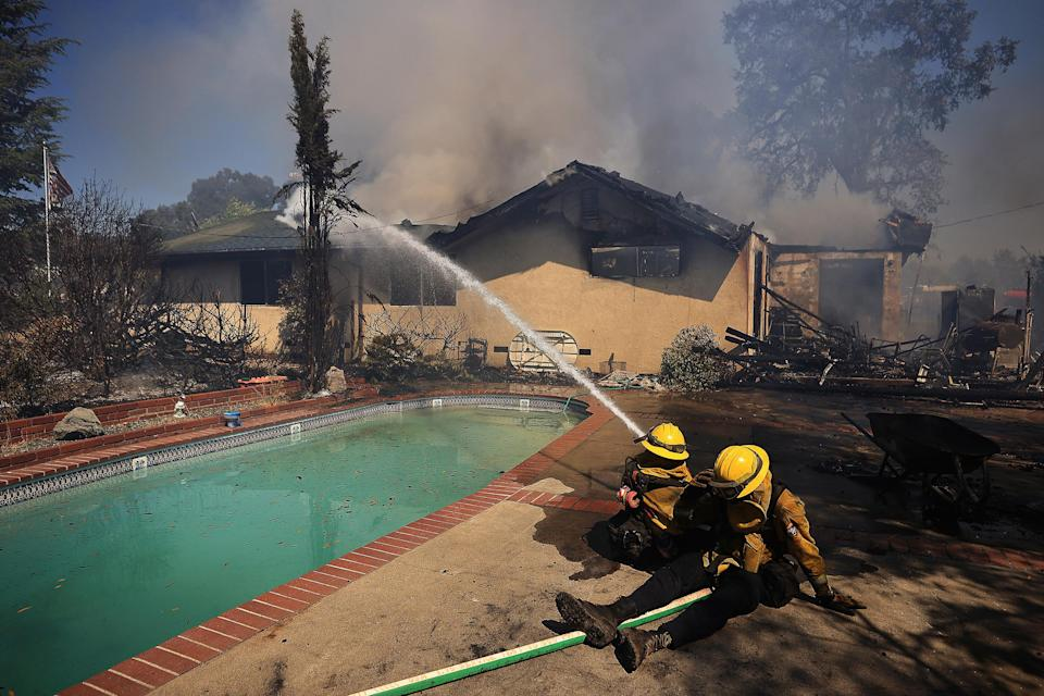 Firefighters take a defensive stand against a home burning in Redwood Valley, Calif., ignited by an 80 acre wind whipped brush fire fed by tinder dry conditions, on July 7.