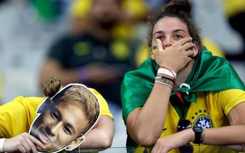 Brazil supporters holding Neymar face masks react after Germany defeated Brazil 7-1 to advance to the finals during the World Cup semifinal soccer match between Brazil and Germany at the Mineirao Stadium in Belo Horizonte - Credit: AP Photo/Andre Penner