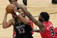 Minnesota Timberwolves center Karl-Anthony Towns, left, looks to the basket against Chicago Bulls forward Patrick Williams during the second half of an NBA basketball game in Chicago, Wednesday, Feb. 24, 2021. (AP Photo/Nam Y. Huh)