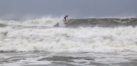 Surfer Ben Powell of Ocean Isle Beach rides a large wave during the effects of Hurricane Arthur, in Ocean Isle Beach, North Carolina July 3, 2014. REUTERS/Randall Hill