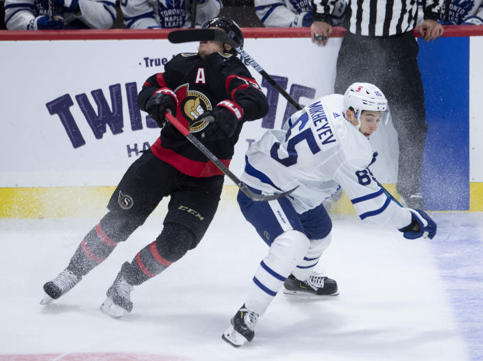 Toronto Maple Leafs right wing Ilya Mikheyev (65) high sticks Ottawa Senators defenseman Thomas Chabot during the second period of an NHL hockey game in Ottawa, Ontario, Saturday, Jan. 16, 2021. Mikheyev received a two-minute penalty on the play. (Adrian Wyld/The Canadian Press via AP)