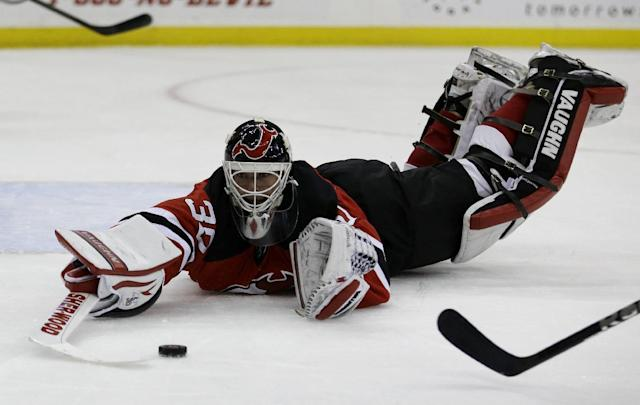New Jersey Devils goalie Martin Brodeur dives to collect a loose puck against the Carolina Hurricanes during the first period of an NHL hockey game, Wednesday, Nov. 27, 2013, in Newark, N.J. (AP Photo/Julio Cortez)