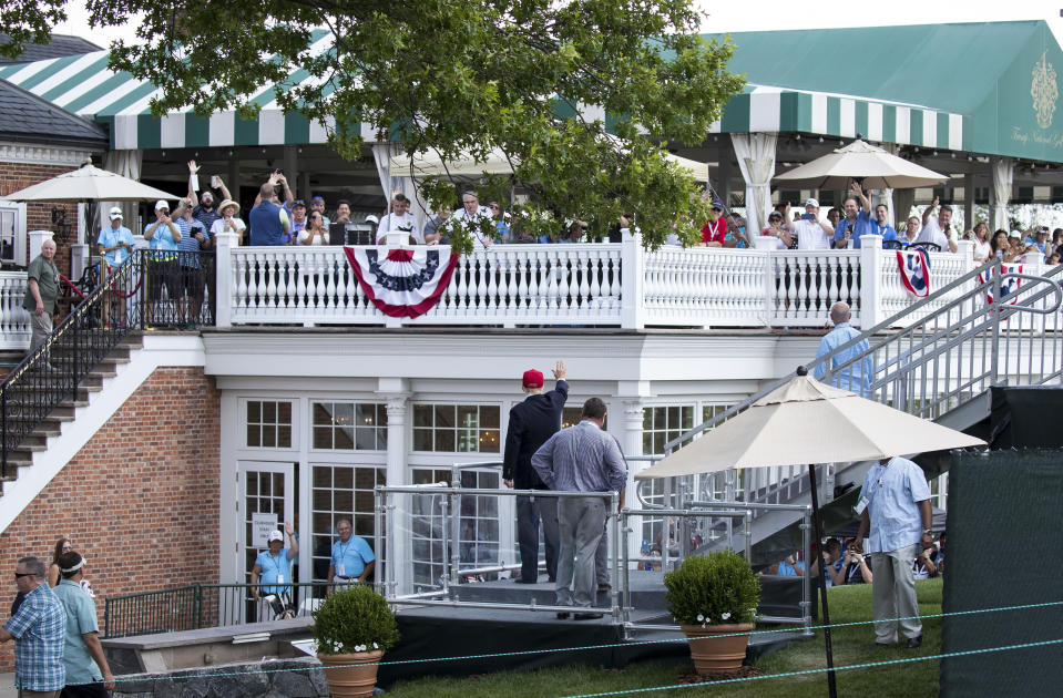 FILE - In this July 15, 2017 file photo, President Donald Trump turns to wave to people gathered at the clubhouse as his walks to his presidential viewing stand during the U.S. Women's Open Golf tournament at Trump National Golf Club in Bedminster, N.J. Trump's true financial picture has gotten renewed scrutiny in the wake of a New York Times report in September 2020 that he declared hundreds of millions in losses in recent years, allowing him to pay just $750 in taxes the year he won the presidency, and nothing for 10 of 15 years before that. (AP Photo/Carolyn Kaster, File)