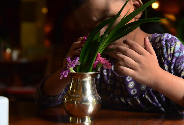 Seven-year-old blind girl who goes under the pseudonym Anna waits at a restaurant with her adoptive mother in Kathmandu on July 23, 2014 (AFP Photo/Prakash Mathema)