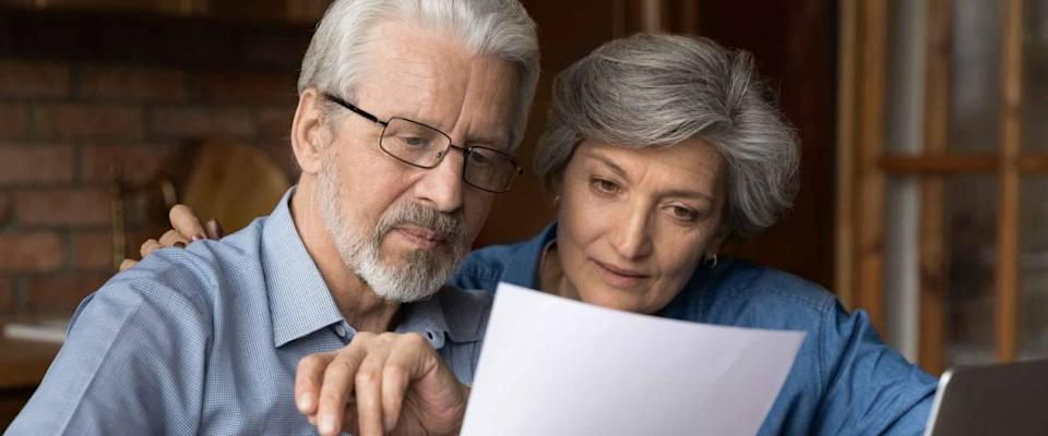 An older couple take a close look at a piece of paper, looking interested.