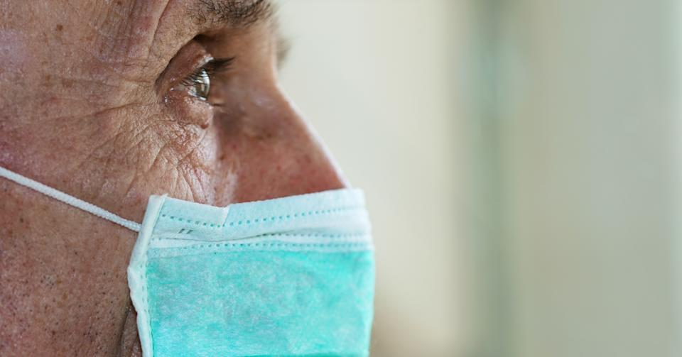 face of elderly man wearing medical facemask health safety concept