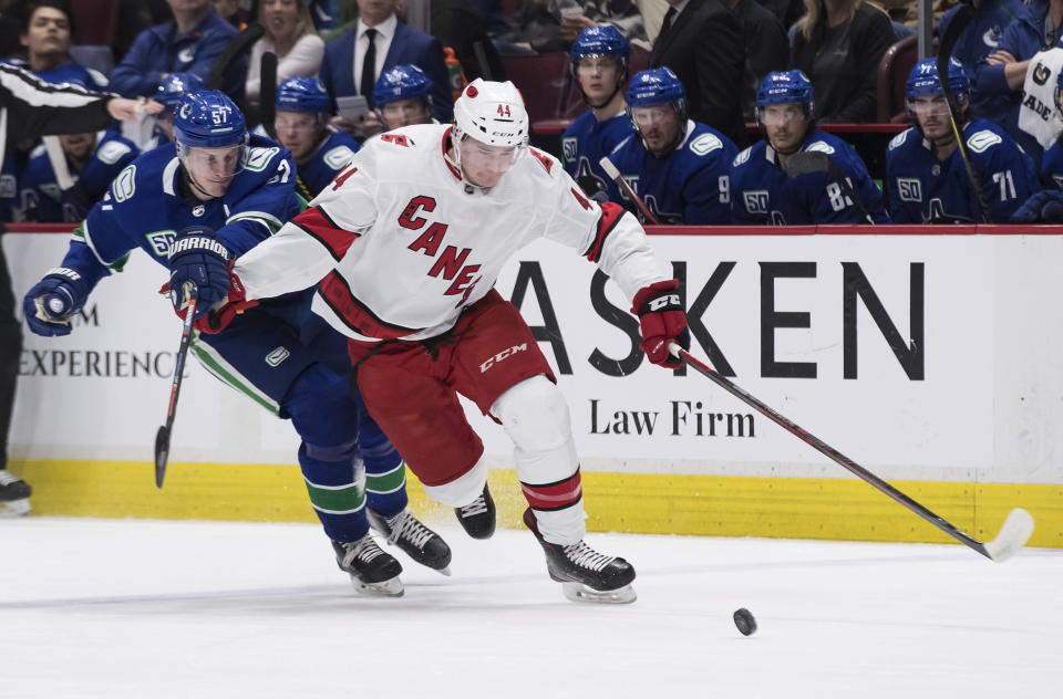 Carolina Hurricanes' Julien Gauthier (44) skates with the puck while being held up by Vancouver Canucks' Tyler Myers during the first period of an NHL hockey game in Vancouver, British Columbia, Thursday, Dec. 12, 2019. (Darryl Dyck/The Canadian Press via AP)