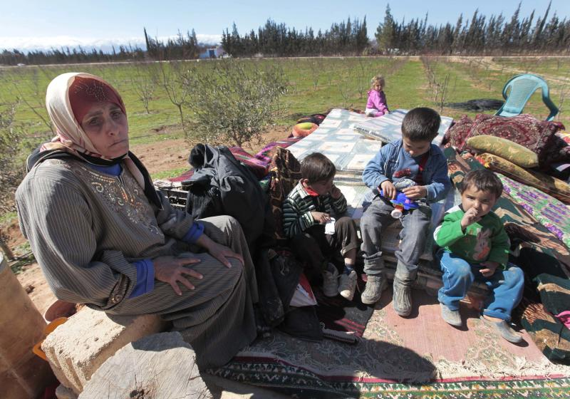 Hassana Abu Firasl, left, a Syrian woman who fled from the Syrian town of Qusair near Homs, is seen with her family at the Lebanese-Syrian border village of Qaa, eastern Lebanon,  Monday, March 5, 2012. More than a thousand Syrian refugees have poured across the border into Lebanon, among them families with small children carrying only plastic bags filled with their belongings as they fled a regime hunting down its opponents. (AP Photo/Hussein Malla)