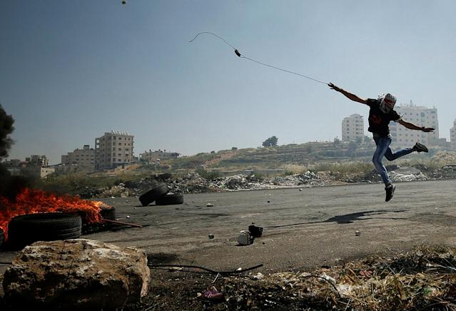 <p>A Palestinian protester uses a sling to hurl stones towards Israeli troops during clashes at a protest in support of Palestinian prisoners on hunger strike in Israeli jails, near the Jewish settlement of Beit El, near the West Bank city of Ramallah May 11, 2017. (Photo: Mohamad Torokman/Reuters) </p>