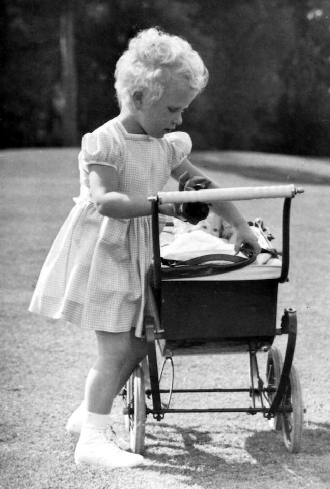 While her mother settled into life as monarch, the little royal enjoyed simple childhood joys — like pushing her baby doll around in a carriage!
