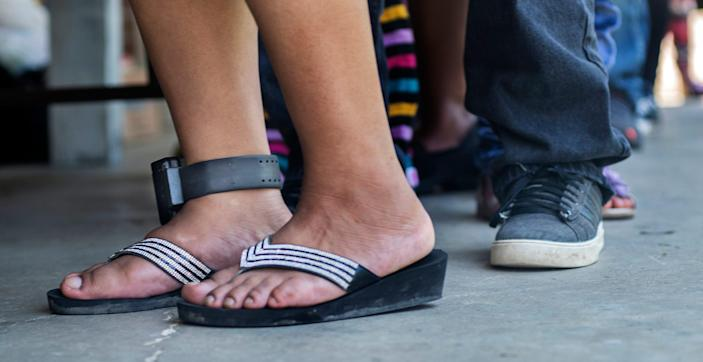 Adelaida Gabriel, of Forest, still wearing an ankle bracelet on from the August 2019 ICE raids, goes through the line for a school supply distribution with her son at Trinity Mission Center in Forest, Miss., Saturday, July 11, 2020.