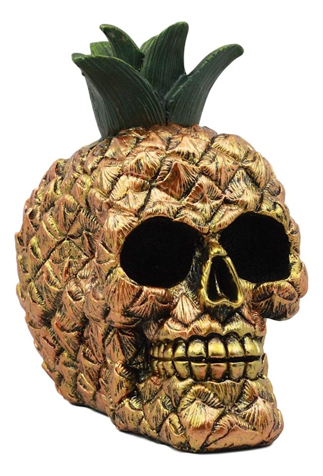 """<p>Made with high-quality polyresin bonded with bronze powder, this tropical <product href=""""https://www.amazon.com/Ebros-Hawaiian-Tropical-Pineapple-Halloween/dp/B079QG5WBS/ref=asc_df_B079QG5WBS/?tag=hyprod-20&amp;linkCode=df0&amp;hvadid=254594830252&amp;hvpos=1o23&amp;hvnetw=g&amp;hvrand=9541452866153689635&amp;hvpone=&amp;hvptwo=&amp;hvqmt=&amp;hvdev=c&amp;hvdvcmdl=&amp;hvlocint=&amp;hvlocphy=1016367&amp;hvtargid=pla-435021708176&amp;psc=1"""" target=""""_blank"""" class=""""ga-track"""" data-ga-category=""""internal click"""" data-ga-label=""""https://www.amazon.com/Ebros-Hawaiian-Tropical-Pineapple-Halloween/dp/B079QG5WBS/ref=asc_df_B079QG5WBS/?tag=hyprod-20&amp;linkCode=df0&amp;hvadid=254594830252&amp;hvpos=1o23&amp;hvnetw=g&amp;hvrand=9541452866153689635&amp;hvpone=&amp;hvptwo=&amp;hvqmt=&amp;hvdev=c&amp;hvdvcmdl=&amp;hvlocint=&amp;hvlocphy=1016367&amp;hvtargid=pla-435021708176&amp;psc=1"""" data-ga-action=""""body text link"""">Ebros Pineapple Skull Figurine</product> ($19) is the perfect combination of festive and frightening. </p>"""