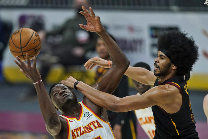 Atlanta Hawks' Clint Capela, left, and Cleveland Cavaliers' Jarrett Allen battle for a loose ball in the first half of an NBA basketball game, Tuesday, Feb. 23, 2021, in Cleveland. (AP Photo/Tony Dejak)