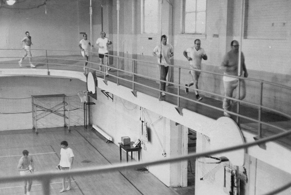 <p>Gym-goers in 1970 are seen jogging around an upper track as others play basketball on the court below. </p>