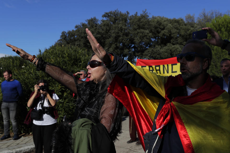 """People make the fascist salute as they gather outside Mingorrubio's cemetery, outskirts of Madrid, Thursday, Oct. 24, 2019. Forty-four years after his demise, the remains of Spanish dictator Gen. Francisco are to be dug out of his grandiose resting place outside Madrid and taken to a small family crypt, finally satisfying a long-standing demand of his victims' relatives and others who suffered under his regime. Inscription at ribbons reads in Spanish """"Barcelona always with Franco"""". (AP Photo/Manu Fernandez)"""
