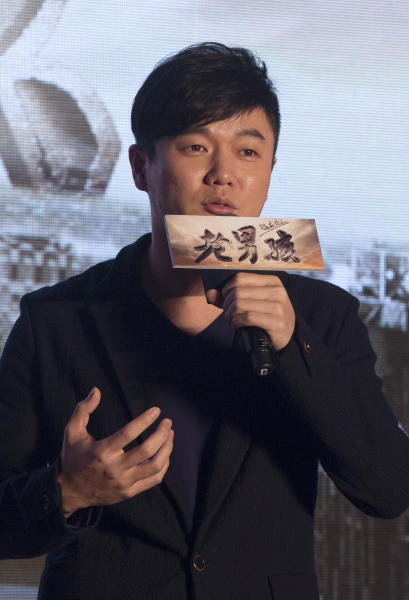 """Chinese film director and actor Xiao Yang speaks on stage as he promote his new movie """"Old Boys: The Way of the Dragon"""" in Beijing Thursday, Jan. 9, 2014. An online microfilm that was watched by millions and helped to establish a genre in China is to be made into a feature-length movie and shown in the country's cinemas. The planned debut of """"Old Boys"""" in China's cinemas in May after ratcheting up almost 70 million views on a video website demonstrates how online films are influencing the traditional film industry. (AP Photo/Andy Wong)"""