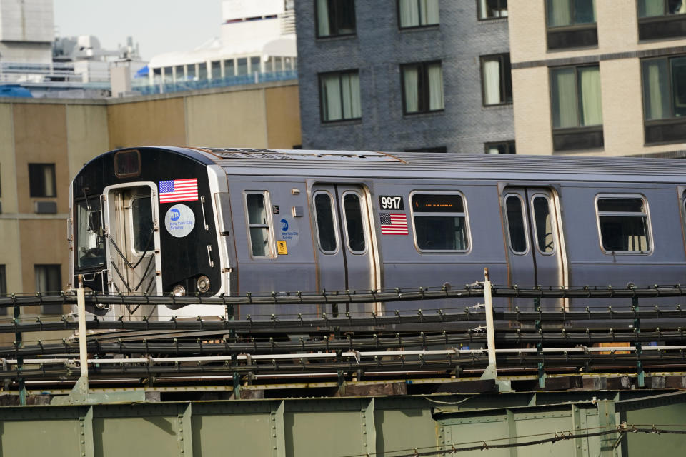 An N train moves through the Long Island City neighborhood Wednesday, Dec. 23, 2020, in the Queens borough of New York. (AP Photo/Frank Franklin II)