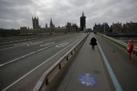 FILE - In this Tuesday, March 23, 2021 file photo, people cros over a quiet Westminster Bridge, backdropped by the scaffolded Houses of Parliament and the Elizabeth Tower, known as Big Ben, in London, during England's third coronavirus lockdown. Thanks to an efficient vaccine roll out program and high uptake rates, Britain is finally saying goodbye to months of tough lockdown restrictions. From Monday May 17, 2021, all restaurants and bars can fully reopen, as can hotels, cinemas, theatres and museums, and for the first time since March 2020, Britons can hug friends and family and meet up inside other people's houses. (AP Photo/Matt Dunham, File)