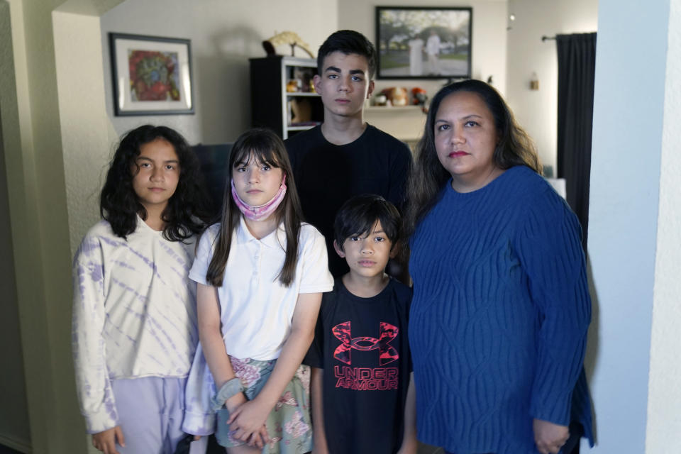 Heather Buen, right, poses for a photo with her children from left, Bayle, Eva, Evan, back and Cody at their home Monday, Oct. 4, 2021, in Fort Worth, Texas. A year and a half in, the pandemic is still agonizing families. There is still the exhaustion of worrying about exposure to COVID-19 itself, and the policies at schools and day cares where children spend their time. (AP Photo/LM Otero)