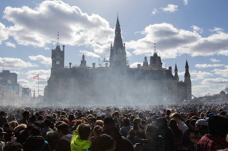 Smoke lingers over Parliament Hill in Ottawa as people smoke marijuana during Canada's annual 4/20 rally in April 2018, six months before the country became just the second in the world to legalize its sale and recreational use (AFP Photo/Lars Hagberg)