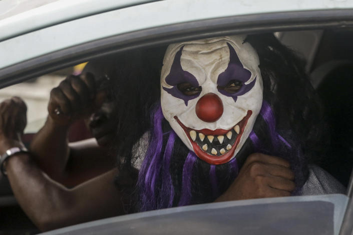 A passenger sits in a car wearing a mask, which he said was to prevent him catching the new coronavirus, in Lagos, Nigeria Friday, March 27, 2020. The new coronavirus causes mild or moderate symptoms for most people, but for some, especially older adults and people with existing health problems, it can cause more severe illness or death. (AP Photo/Sunday Alamba)