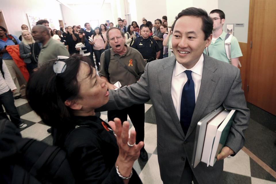 """FILE - In this Monday, Aug. 17, 2009 file photo, protesters confront John Yoo, a constitutional law professor at the University of California, Berkeley, as he makes his way to a classroom in Berkeley, Calif. About 75 demonstrators called for the university to fire Yoo, a former Bush administration attorney, who wrote legal memos used to support harsh interrogation techniques that critics say constituted torture. As deputy assistant attorney general in the Justice Department's Office of Legal Counsel, Yoo provided much of the legal underpinning for the War on Terrorism. He argued that """"enemy combatants"""" captured in Afghanistan need not be given prisoner of war status; that the president could authorize warrantless wiretaps of U.S. citizens on American soil; that the use of """"enhanced interrogation techniques"""" like waterboarding was within the power of the president during wartime. (AP Photo/Noah Berger)"""