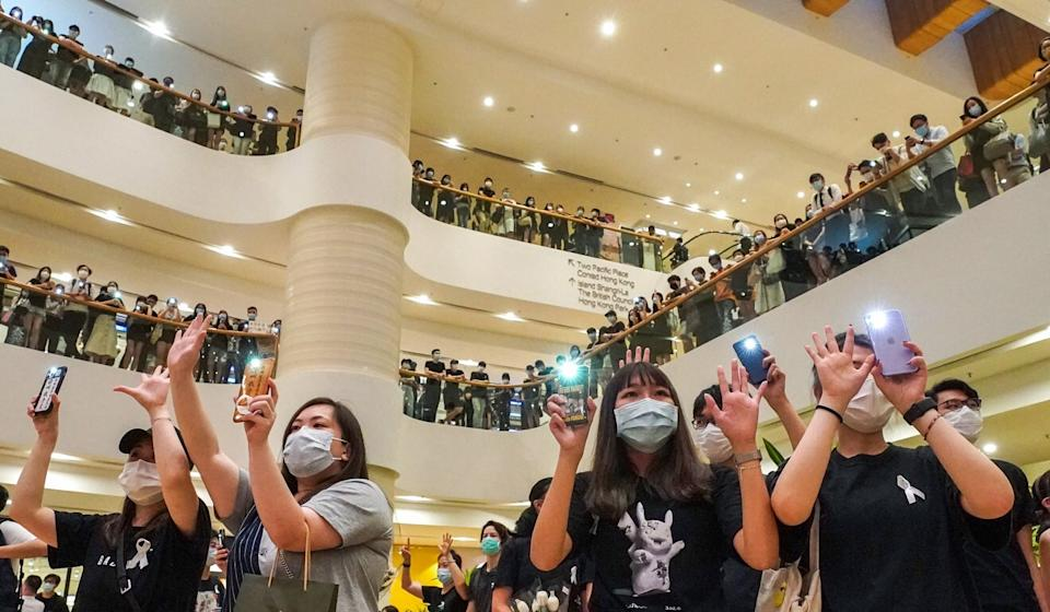 Protesters gather inside Pacific Place and hold up their palms signifying the five demands. Photo: Felix Wong