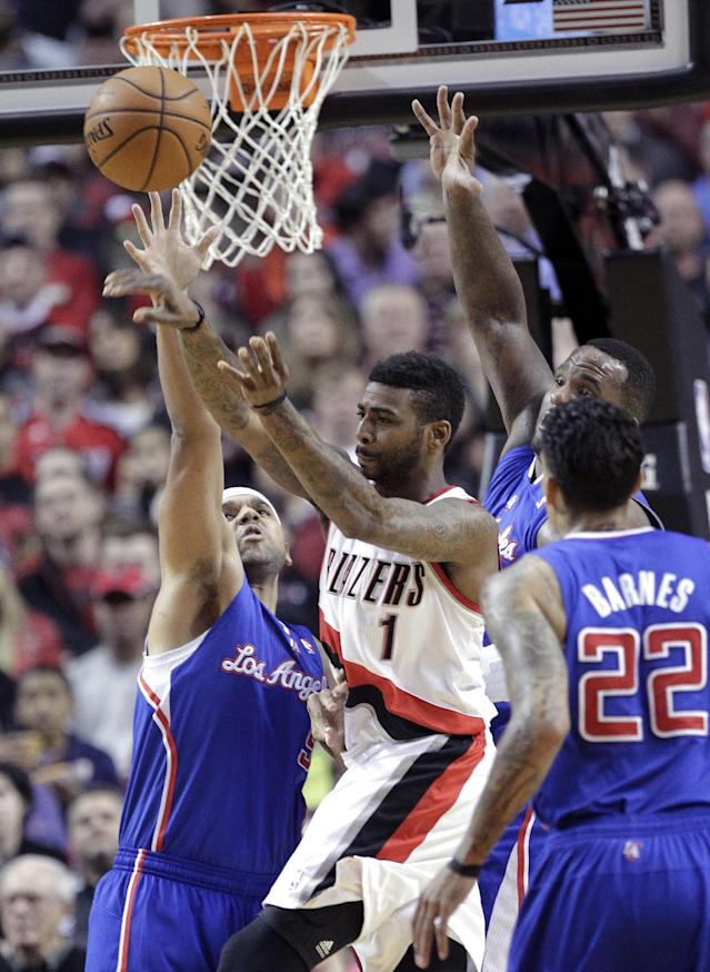 Portland Trail Blazers forward Dorell Wright (1) passes off against defense from the Los Angeles Clippers' Jared Dudley, left, Matt Barnes, right, and Glen Davis during the first half of an NBA basketball game in Portland, Ore., Wednesday, April 16, 2014. (AP Photo/Don Ryan)
