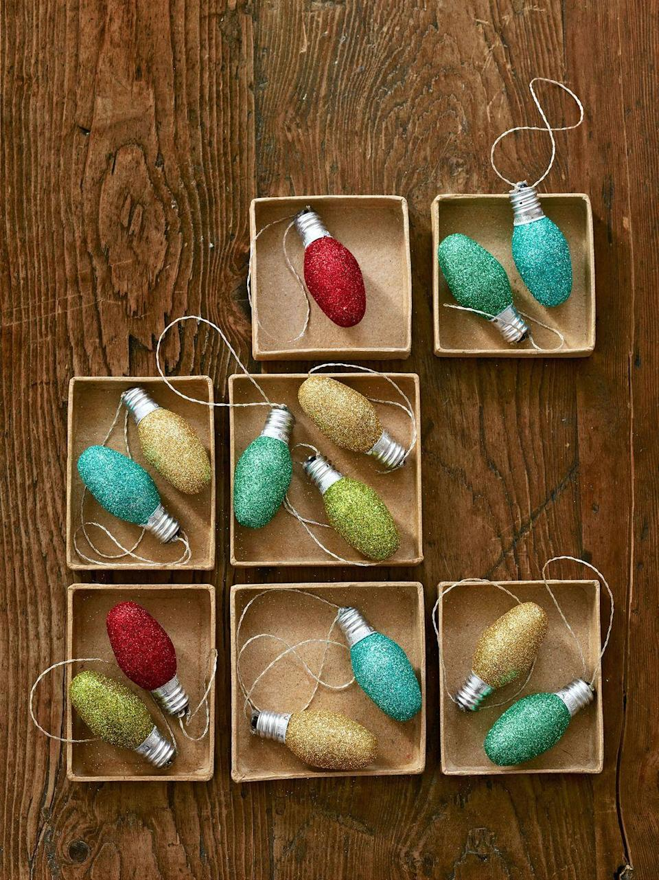 """<p>These shimmery ornaments get their twinkle from a coat of glitter, so there's no chance of one burning out.</p><p>Get the tutorial at <em><a href=""""https://www.countryliving.com/diy-crafts/how-to/g1798/recycled-crafts-holiday-decor/?slide=1"""" rel=""""nofollow noopener"""" target=""""_blank"""" data-ylk=""""slk:Country Living"""" class=""""link rapid-noclick-resp"""">Country Living</a>.</em></p>"""
