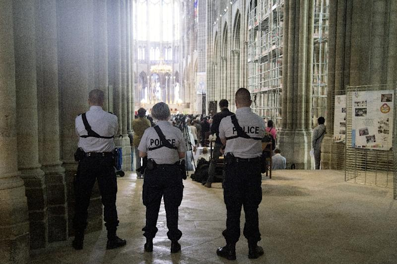 Police officers stand guard during mass in Saint-Denis Cathedral on July 31, 2016 (AFP Photo/Dominique Faget)