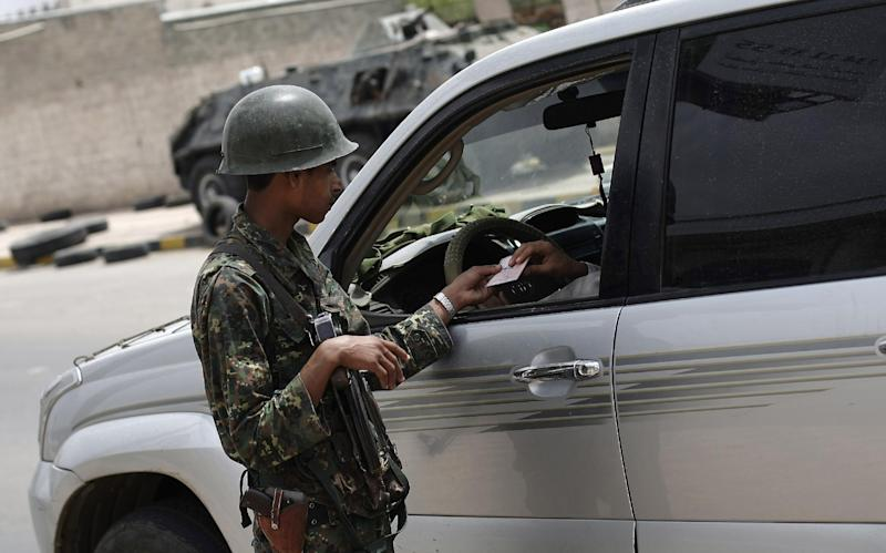 A Yemeni police trooper inspects documents at a checkpoint amid an increase in security following an announcement last week by Yemeni authorities that they had discovered an al-Qaida plot to target foreign embassies and international shipping in the Red Sea, in Sanaa, Yemen, Monday, Aug. 12, 2013. The leader of the Yemen-based al-Qaida offshoot vowed in a message posted Monday to free fellow militants from prisons and urged jailed fighters to remain faithful to the terror group's ideology. (AP Photo/Hani Mohammed)