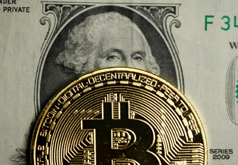 A Bitcoin and Dollar note are seen in this illustration picture