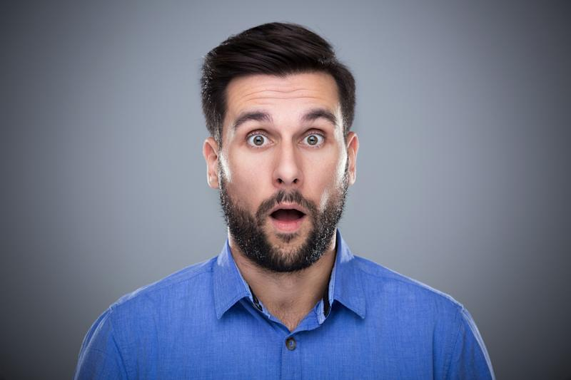 A man win a blue shirt with his mouth open, giving a look of surprise.