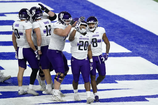 Northwestern running back Cam Porter (20) celebrates after scoring during the first half of the Big Ten championship NCAA college football game against Ohio State, Saturday, Dec. 19, 2020, in Indianapolis. (AP Photo/Darron Cummings)